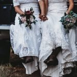 Two brides sitting in the back of a truck wearing boots and holding bouquets